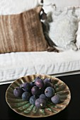 Purple figs on ceramic dish; pale sofa with scatter cushions in background