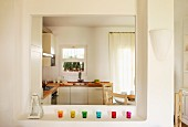 Colorful glass candle holders on a shelf in front of an wide serving hatch and view into a bright, modern kitchen