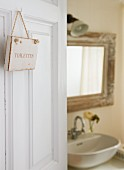 Sign reading 'Toilettes' on open door showing view of washstand and mirror beyond