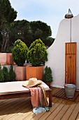 Patio lounge with a straw hat in front of a small tree in a pot in the corner of the terrace of a Mediterranean home with an outdoor shower