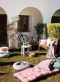 Sunbathing in a front yard with pillows and patio furniture pads on the grass in front of a Mediterranean home with an arcade