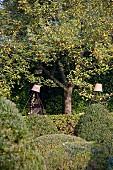 Garten mit formgeschnittenen Pflanzen & Tontöpfen auf Stäben als Gartendeko