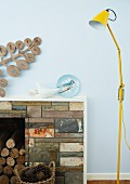 Yellow, retro floor lamp next to an open fireplace with natural stone apron in front of a bright blue wall