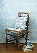 Pillows on a DIY tree branch chair next to stack books on the floor in front of a wall with bright blue wall paper with a floral pattern