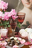 Meringues, chocolates, wine glasses, candles and potted cyclamen