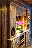 Potted orchid in serving hatch integrated into rustic, wooden fitted cupboard with carved details