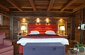 Modern double bed with upholstered headboard against wall in rustic wooden cabin