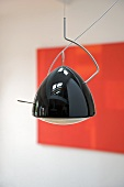 Modern pendant lamp with black glossy casing and modern picture in background
