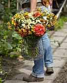 Woman carrying summer bouquet of dahlias, alstroemeria and rudbeckia