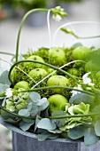 Blumenarrangement mit grünen Äpfeln, Eukalyptus, Moos und Milchsternen