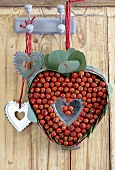 Heart made of leaves and rosehips and metal hearts hanging on hooks on wooden wall