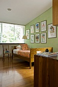Bedroom with skilfully crafted bed in front of framed posters on wall painted lime green