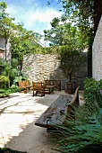 Bench carved from natural tree trunk and seating area in sheltered courtyard with high stone walls