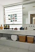 White marble bathroom with bottles on long washstand and photos on frosted glass window next to large wall-mounted mirror