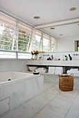 White marble bathroom with mirrored wall above washstand and angled exterior blinds on windows along one side