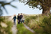 Family and dog walking along farm track