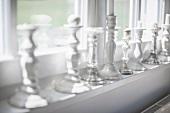 Many different candlesticks on windowsill