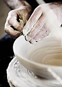 A potter creating a clay bowl on a potter's wheel