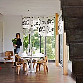 Seating area with 50s-style wooden chairs in corner of room with view of garden and woman carrying vase of flowers