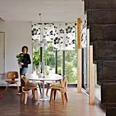 Sitzplatz mit Holzstühlen im 50er Jahre Stil in Zimmerecke mit Gartenblick und eine Frau mit Blumenvase in den Händen