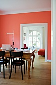 Dark wooden chairs at antique dining table in room with walls painted salmon pink and wide doorway