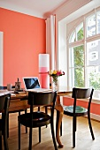 Work area on antique wooden table next to window in room with salmon pink wall
