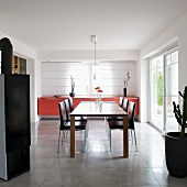Modern dining table and leather-covered chairs in front of red sideboard against closed panel curtains on windows
