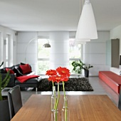 Single red gerbera daisies in bottles on dining table below pendant lamps with frosted glass shades and designer lounge area in background