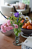 Summer posy in glass vase and fruit bowl on table