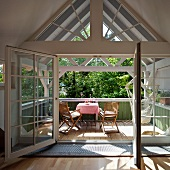 Soaking up the sun on a balcony - attic room with open balcony door and view of sunny balcony with table and chairs