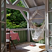 Relaxing in a hammock - view of sunny balcony through open door of wooden house