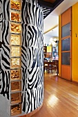 Foyer with zebra patterned curved wall and yellow-painted wall next to open-plan dining room