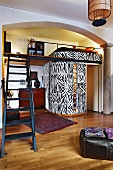 Open-plan interior with steel staircase and mezzanine above installation with zebra-patterned walls
