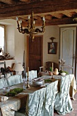 Dining area in rustic kitchen-dining room festively decorated with elegant fabric draped on long dining table and romantic covers on chairs