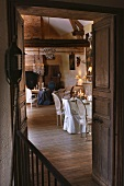 View through open double doors of dining area and seating area in front of fireplace in traditional interior