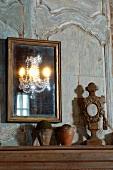 Spiegel mit Goldrahmen an Vintage Holzpaneel und Tontöpfe neben Holzskulptur auf Ablage