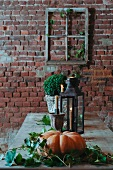 Arrangement of leaves around pumpkin and lit candle in lantern on table in front of rustic brick wall