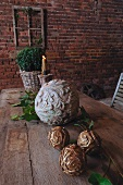 Balls of wood and stone carved with floral patterns on rustic table in front of brick facade