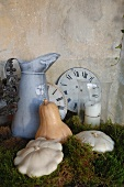 Antique water jug, old clock faces and pumpkins on bed of moss as romantic country house decoration