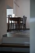 Schlichter Esstisch mit Stühlen unter Pendelleuchte am Fenster