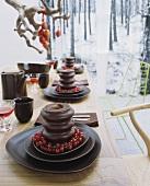 Gestaltete Dessert-Gedecke auf Esstisch - Baumkuchen mit Johannisbeerrrispen auf Schalenset aus dunkelbrauner Keramik