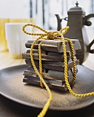 A yellow cord tied around pieces of chocolate, on a ceramic dish in front of a vintage coffee pot