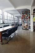 Besprechungstisch auf Rollen und hohe Regalwand im grosszügigen, hellen Loftraum mit Industriefenstern
