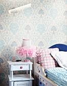 Kinderbett aus bemaltem Holz vor traditionell gemusterter Tapete und Nachttisch im romantischen Vintagelook mit tüllverziertem Lämpchen