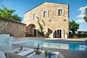Chillen auf schattiger Terrasse - Getränke auf Beistelltischen vor Pool im Innenhof einer mediterranen Wohnanlage
