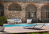 Designer lounger on wooden deck next to pool and white seating in front of Mediterranean house