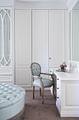 Ottoman, white dressing table with upholstered chairs and fitted wardrobe in dressing room