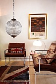 Vintage leather armchair and couch, both with stainless steel frames, and spherical glass light fitting in living room