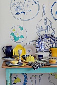 Blue, white and yellow crockery on a table against a wall poster decorated with a crockery motif in the same colours