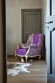 View through open door of Rococo-style reading chair with colourful, spotted designer upholstery in corner of room against door